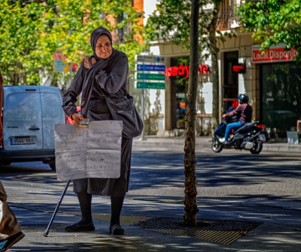 Spanish beggar standing in front of a street side cafe in Madrid, Spain.