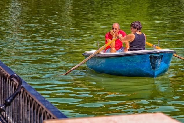 Couple row a boat in Estanque Grande del Retiro of Parque de El Retiro in Madrid, Spain.